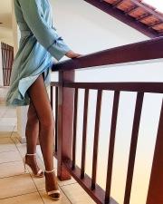 Julia sul balcone in collant e sandali