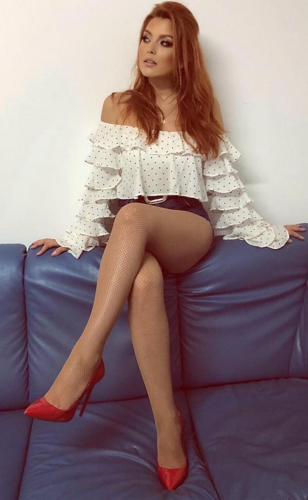 Elena Gheorghe sul divano con le calze a rete