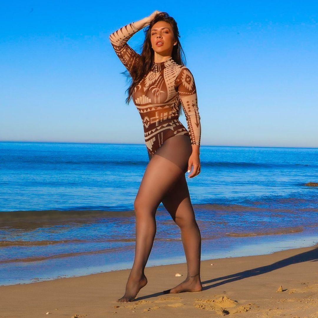 Miss agosto sulla sabbia in collant neri