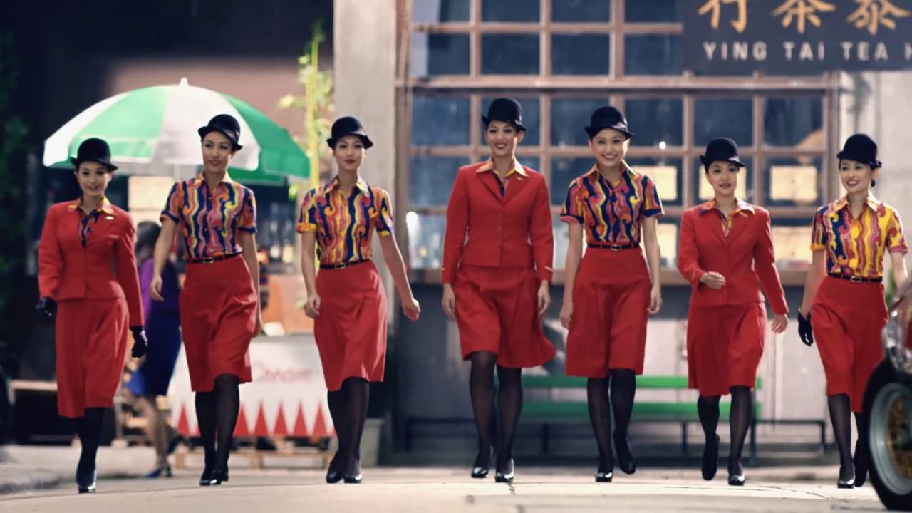 Stewardess Cathay Pacific in gonna rossa e collant neri